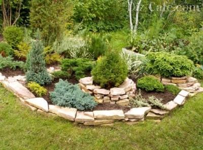 Плоские камни скрепляют между собой цементным раствором, хотя если ограждение будет невысоким, то можно просто уложить их друг на дружку