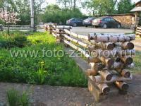 Берёзовая поленница на столбах, берёзовые стволы в пролётах - ограда цветочного палисадника готова!