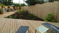 Гармоничный сад с экзотической палубой деревянной доски